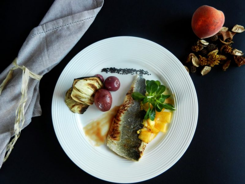 Spigola con riduzione al bellini, insalata di songino e pesche, patate magenta al vapore e chips di melanzane